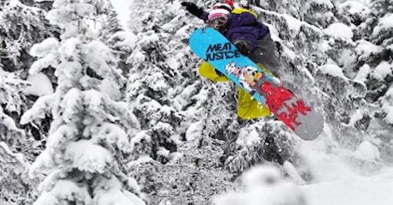 A snowboarder hitting a jump at Red Mountain Resort - Rams Head Inn