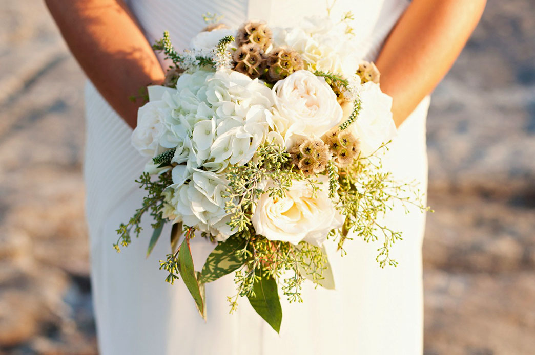 A bride holds a bouquet of flowers at an outdoor wedding at the Rams Head Inn at Red Mountain